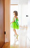 Child in room with green fairy costume