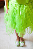 Lower half length shot of child in green fairy costume
