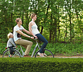Family with one child riding on bicycle together
