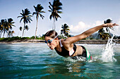 Mid adult triathlete swimming in sea