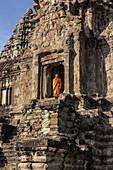 Young Buddhist monk standing at temple in Angkor Wat, Siem Reap, Cambodia