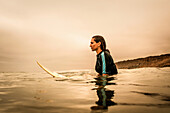 Young woman in sea with surfboard, profile