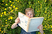 Boy lying on grass reading book