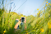 Boy lying in long grass playing on smartphone