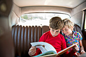 Boys sitting in back of car reading book