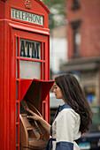 Mid adult women using cash machine in a public telephone box
