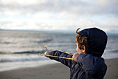 Boy catapulting rock out to sea