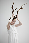 Girl posing with antlers on head