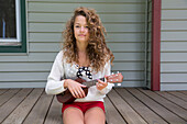 Teenage girl sitting on porch holding miniature guitar