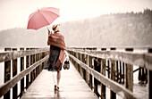 Woman with pink umbrella strolling on pier, Bainbridge Island, Washington, USA