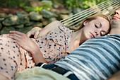 Young couple asleep in hammock