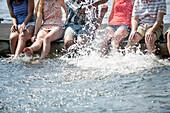 Friends sitting on jetty splashing in lake