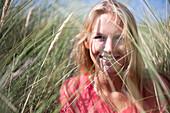 Portrait of blonde woman in marram grass, Wales, UK