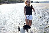 Woman walking dog on beach, Wales, UK