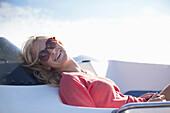 Woman wearing sunglasses laughing on yacht, Wales, UK