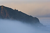 Point Sur Lighthouse and morning fog at sunrise, Big Sur, Monterey County coast, California.