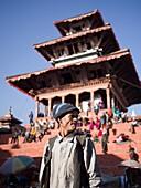 Pedestrians walk and travel by cart down a street in Kathmandu, Nepal.