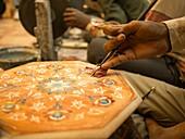 Man using hand tool to design a marble in Agra, Uttar Pradesh, India.