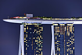Marina Bay Sands Skypark at night. The SkyPark is a partially suspended rooftop deck, located on the top of Marina Bay Sands Hotel, that include a swimming pool, a bar, an obervation deck and a restaurant. Singapore.