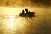 Two fishermen in the Finnish Gulf, sunrise. Primorsk, Russia.