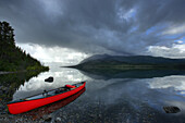 Canoe With Traveling Gear And Storm Clouds On Kusawa Lake, Yukon