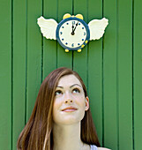 Young Woman Looking Up At Clock As Time Flies, Ontario