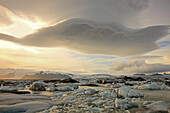 The Melting Icebergs Of Jokulsarl On The Glacial Lagoon In Southern Iceland With Lenticular Clouds Above Them
