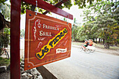 'The Parrilla Grill, Las Piedras Restaurant Sign Hanging And Surfers Ride Past On Their Bicycles In Santa Teresa And Mal Pais (Malpais) On The Nicoya Peninsula; Puntarenas Province, Costa Rica'