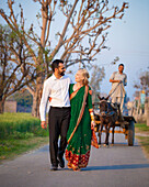 'A Mixed Race Couple Walking In An Embrace Down A Path; Ludhiana, Punjab, India'