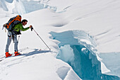 Skier Probing Edge Of A Dangerous Crevasse On The Upper Triumvirate Glacier, Tordrillo Mountains, Winter In Southcentral Alaska