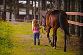 Young Girl Walking With A Horse On A Grassy Path, Kodiak, Southwest Alaska, Summer