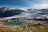View Of A Mountain Pond In Front Of Exit Glacier And Harding Ice Field, Kenai Fjords National Park, Kenai Peninsula, Southcentral, Alaska