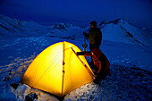 Climbers Enter A Lit Tent To Spend The Night At Camp In The Chugach Mountains Near Anchorage, Chugach State Park, Southcentral Alaska, /Nspring