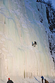 Evening Light Shines On An Ice Climber As He Repels Down An Ice Waterfall Along Turnagain Arm, Southcentral Alaska, Winter