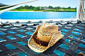 'A sunhat on the hammock of a catamaran off the coast of an hawaiian island; Hawaii, United States of America'