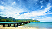 'A pier leading out from the beach to a covered structure; Hawaii, United States of America'
