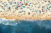 Aerial view of a busy beach with a colourful assortment of umbrellas and towels