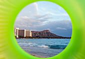 'View of Diamond Head seen through a green inflatable tube; Waikiki, Oahu, Hawaii, United States of America'