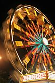 'Ferris wheel illuminated in colourful lights at night; Honolulu, Oahu, Hawaii, United States of America'