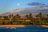 'An outrigger canoe in Kukio Bay with a view of Mauna Kea in the distance; Big Island, Hawaii, United States of America'