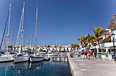 'Boats In The Harbour And Pedestrians On The Promenade; Puerto Morgan, Gran Canaria, Spain'