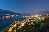'Buildings Along Lake Maggiore And The Swiss Alps Illuminated By Moonlight At Night; Locarno, Ticino, Switzerland'