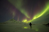 'A Person Stands On The Frozen Blackstone River Beneath The Northern Lights; Yukon, Canada'