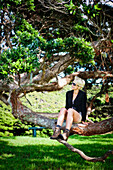 'A Young Woman Sits In A Tree On An Island In The Bay Of Islands; Urupukapuka Island, New Zealand'