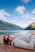 'A Girl Lies Down On A Picnic Table And Enjoys The Sun With A Sailboat In Lake Rotoiti In The Background, Tasman Region; New Zealand'