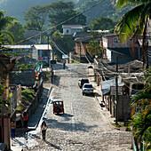 'A Street With Pedestrians, Cars, Buildings And Lush Vegetation; Copan, Honduras'