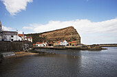 'Houses Along The Water's Edge And A Rock Cliff; Staithes, Yorkshire, England'