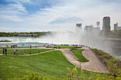 'Visitors Stand Behind A Railing Overlooking Horseshoe Falls At Niagara Falls State Park, In New York State With The Town Of Niagara Falls, Ontario In The Background; Niagara Falls, New York, United States Of America'
