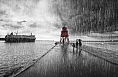 'A family walking in the pouring rain along harbour beach with Groyne Lighthouse and a ship; South Shields, Tyne and Wear, England'