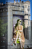 Reflection of a mannequin in the window of the dior boutique, rue francois 1er, 8th arrondissement, paris, france